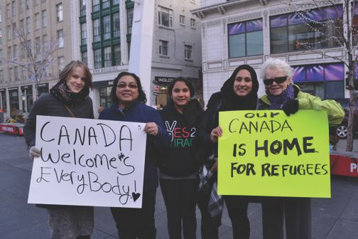 Pansey Hasan, left, and daughter Ranyah Hasan, fourth from left, demonstrate at Yonge-Dundas Square to tell Canadians and Ottawa they support Syrian refugees. Gerald V. Paul photo.