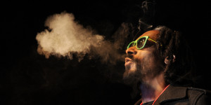 """DENVER, CO - APRIL 19: Snoop Lion exhales a heart shaped cloud of marijuana smoke while doing a Q&A with the audience after the screening of his documentary Reincarnated during the first ever """"Green Carpet"""" event as a part of the High Times US Cannabis Cup at the Fillmore Auditorium on April 19, 2013 in Denver, Colorado. (Photo by Seth McConnell/The Denver Post via Getty Images)"""