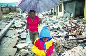 With A boy and a woman walk next to remains of houses destroyed by Hurricane Matthew in Baracoa