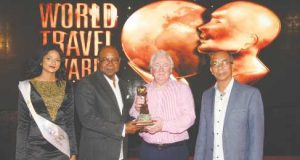 Tourism Minister Edmund Bartlett (2nd left) receives the award of World's Leading Personality for Outstanding Services to Travel from World Travel Awards President and Founder, Graham Cooke (2nd right). Minister without portfolio in theJamaica's Ministry of Economic Growth and Job Creation, Dr Horace Chang (right)